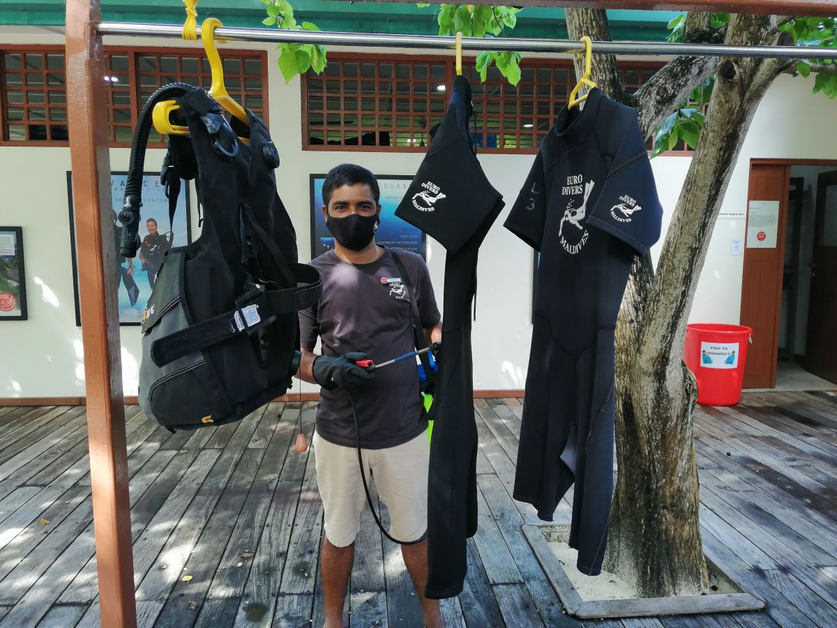Team member cleaning wet suits at Vilamendhoo Island Resort & Spa in the Maldives