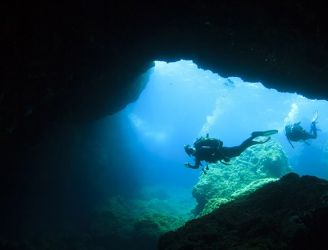 Divers by a cave entrance in Malta