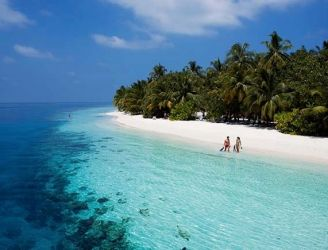 Couple on a beach at Vilamendhoo Resort in the Maldives