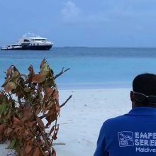 Crew member looking out to Emperor Serenity liveaboard in the Maldives